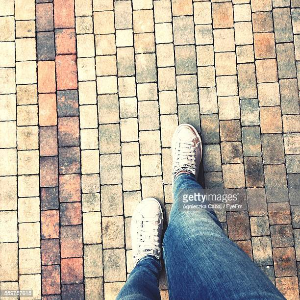 Feet Of Man Walking On Pavement