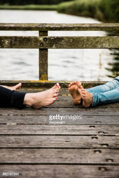 Feet of mother and daughter on jetty at a lake