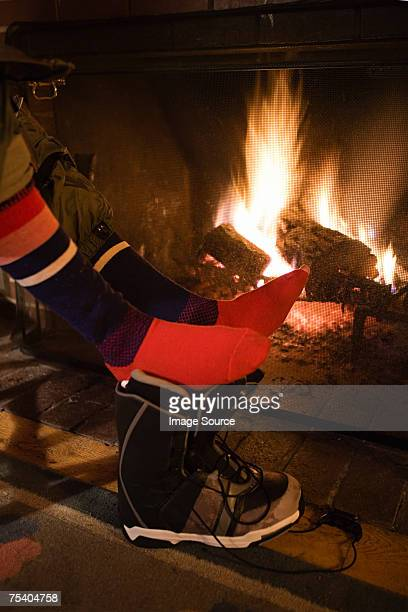 feet of person by fire - apres ski stock pictures, royalty-free photos & images