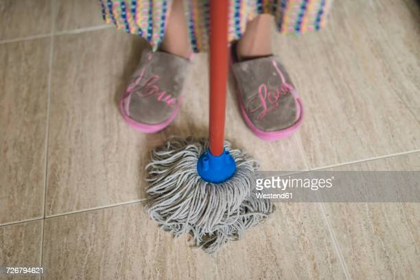 Feet of senior woman with cleaning mop