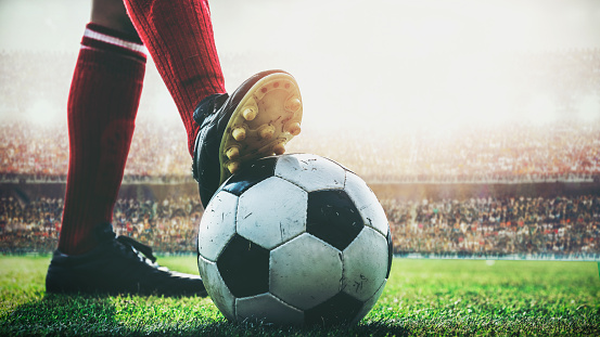 feet of soccer player tread on soccer ball for kick-off in the stadium 992892836