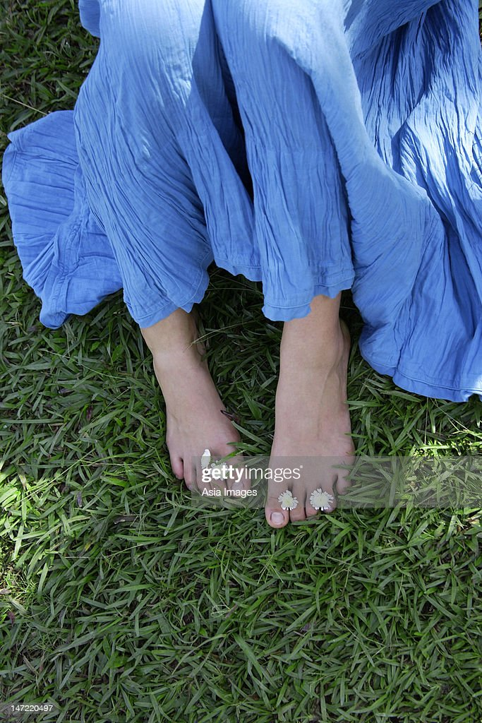 Feet of teen girl with flowers between toes : Stock Photo