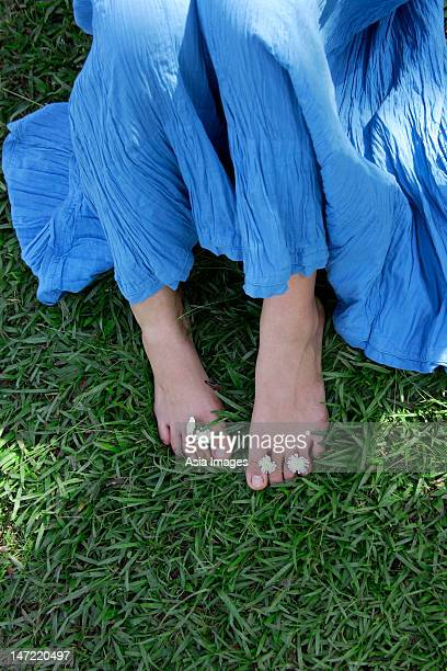 Feet of teen girl with flowers between toes