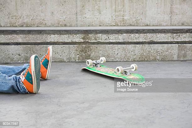 Feet of teenager who has fallen off skateboard