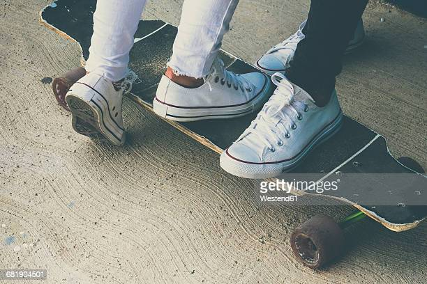 feet of two teenagers on skateboard - petite amie photos et images de collection