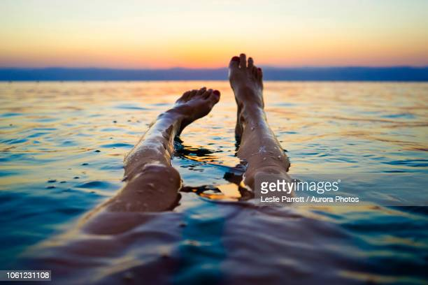 feet of woman floating in dead sea at sunset, madaba governorate, jordan - standing water stock pictures, royalty-free photos & images