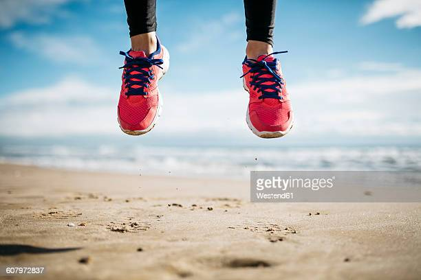 feet of woman jumping on beach - leichter stock-fotos und bilder