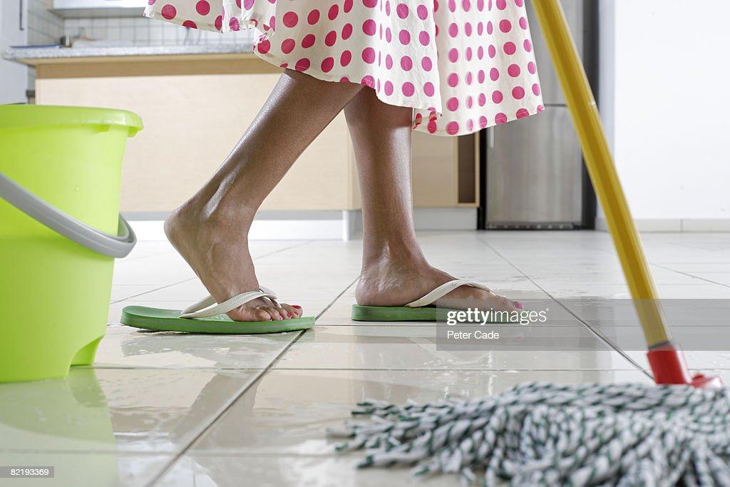 Feet of woman mopping kitchen : Stock Photo