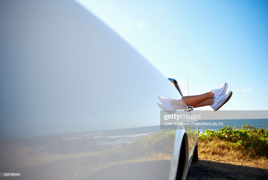 Feet of woman protruding from convertible on beach : Foto stock