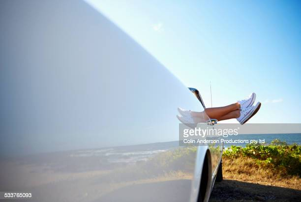 Feet of woman protruding from convertible on beach