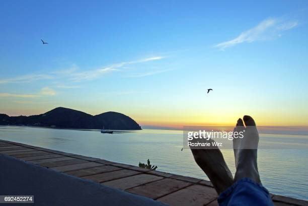 Feet of woman relaxing against rising sun
