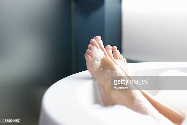 Feet of woman relaxing in bubble bath