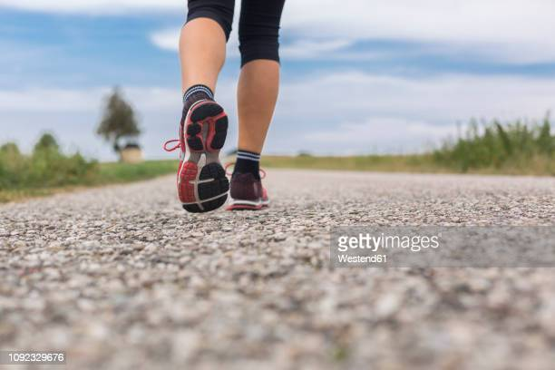 Feet of woman running on remote country lane in summer