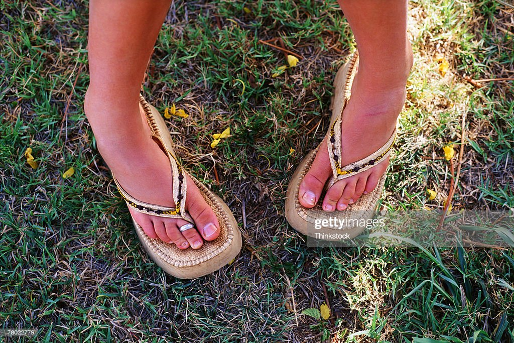 Feet of woman wearing sandals standing pigeon-toed : Stock Photo