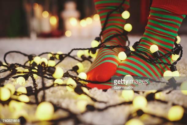 78d0c0a1c84 Feet Of Woman Wearing Stripy Socks Tangled In Fairy Lights Stock Photo