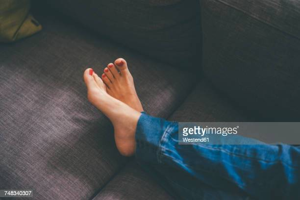 feet of young woman lying on couch at home - barefoot stock pictures, royalty-free photos & images