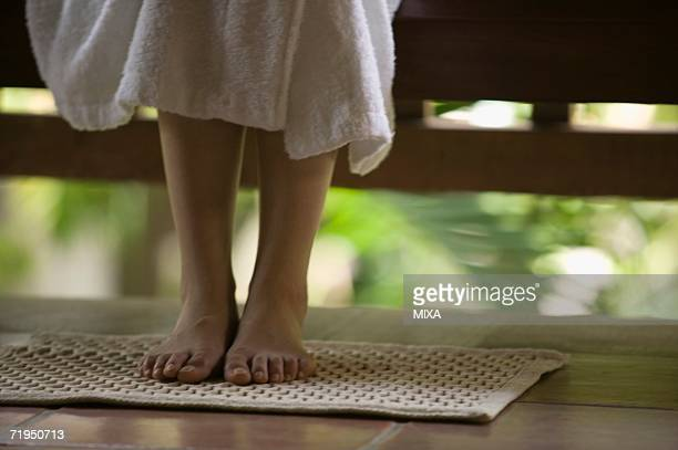 Feet of young woman on bath mat