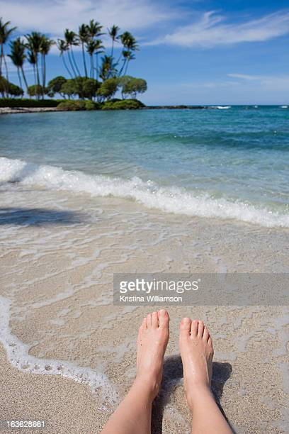 Feet of young woman relaxing on the coast