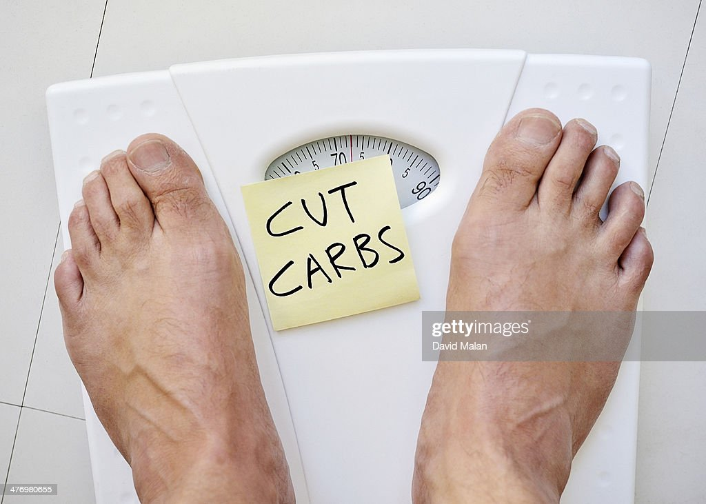 Feet on a scale with 'cut carbs' note : Stock Photo