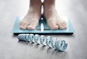 Feet on bathroom scale with tape measure