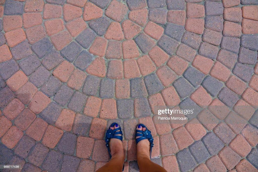 Feet on brick circular-pattern floor : Stock-Foto