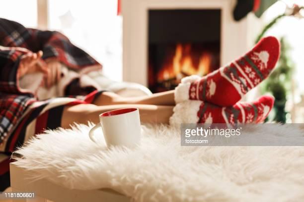 füße auf weihnachtssocken in der nähe von kamin - hygge stock-fotos und bilder