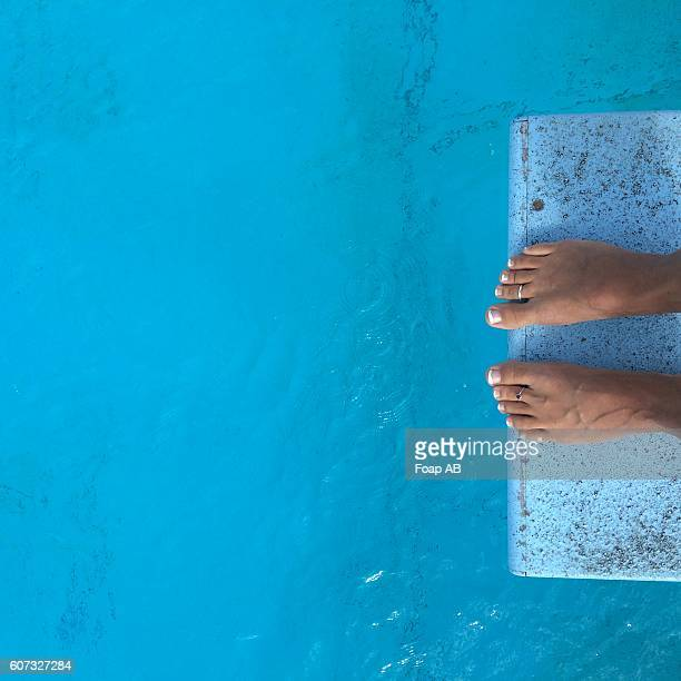 Feet on diving board above the swimming pool