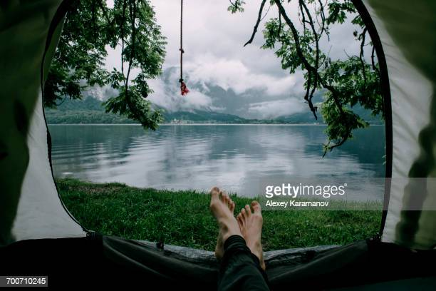 feet on man laying in camping tent at lake - mujeres fotos stock pictures, royalty-free photos & images