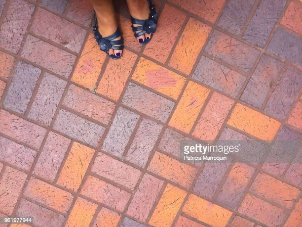 Feet on multicolored brick