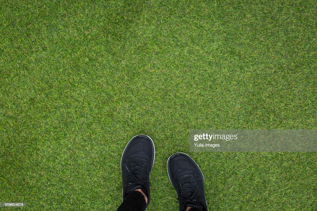 Feet on person in black trainers on grass : Stock-Foto