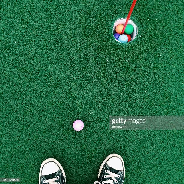 feet on putting green - miniature golf stock photos and pictures