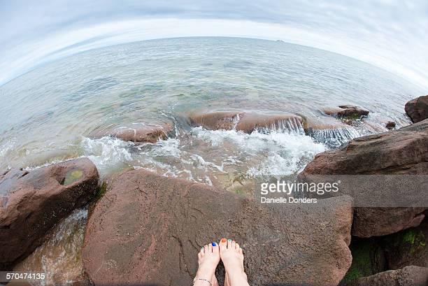 Feet on rocks at the beach through a fish-eye lens