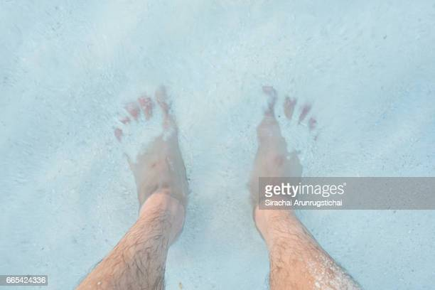 Feet on the sand in shallow water