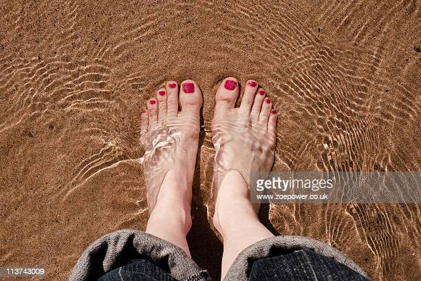 feet paddling in the sea with gentle ripples - rolled up trousers stock pictures, royalty-free photos & images