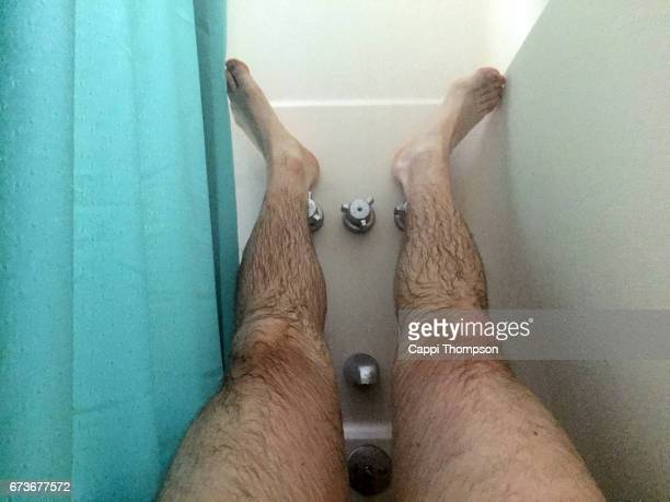 feet resting in the shower - homme poilu photos et images de collection