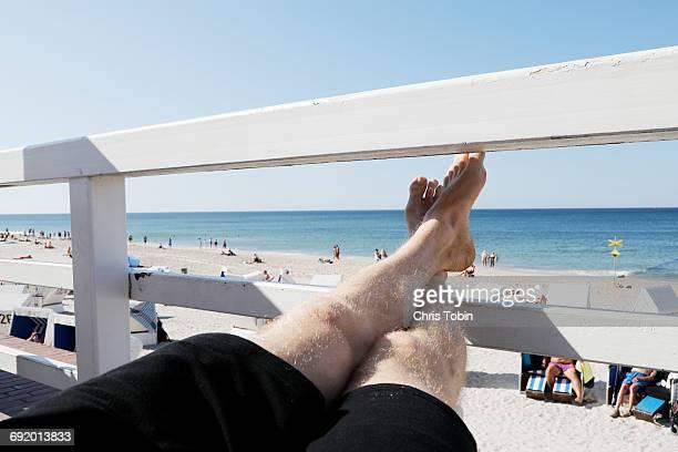 Feet resting on fence