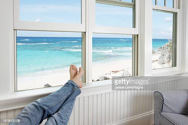 Feet resting on the sill of a window facing the beach