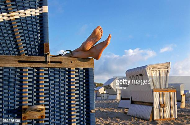 Feet sticking out from roofed wicker beach chair at Sylt North Frisian Island SchleswigHolstein Germany