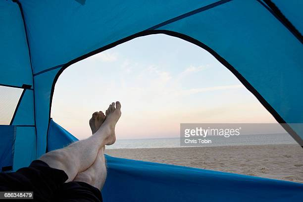 Feet sticking out of tent at beach