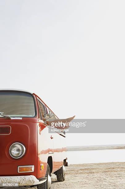 Feet sticking out of van window on beach
