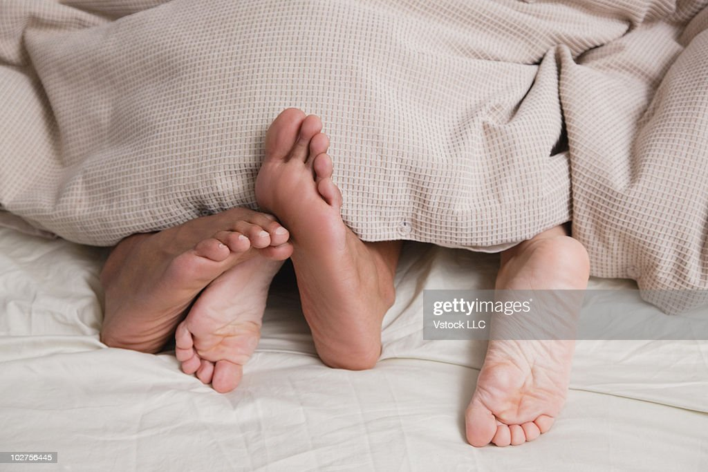 Feet under covers in bed : Stock Photo