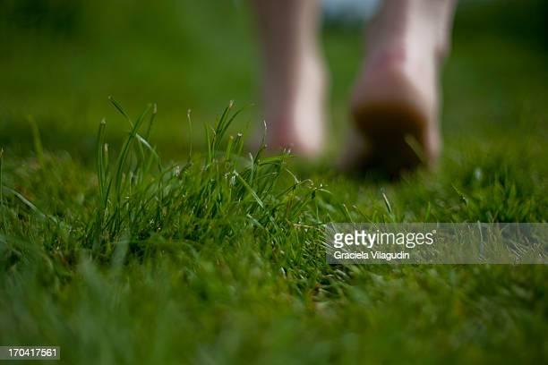 Feet walking on grass in a park
