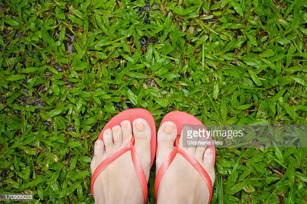 Feet wearing orange sandals on the grass