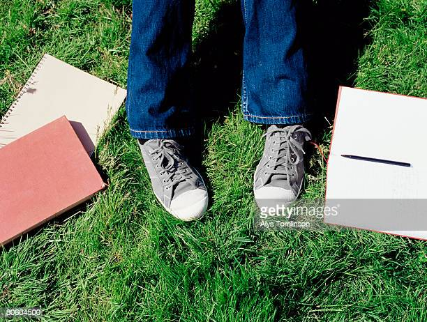 feet with textbooks on lawn - human foot stock pictures, royalty-free photos & images