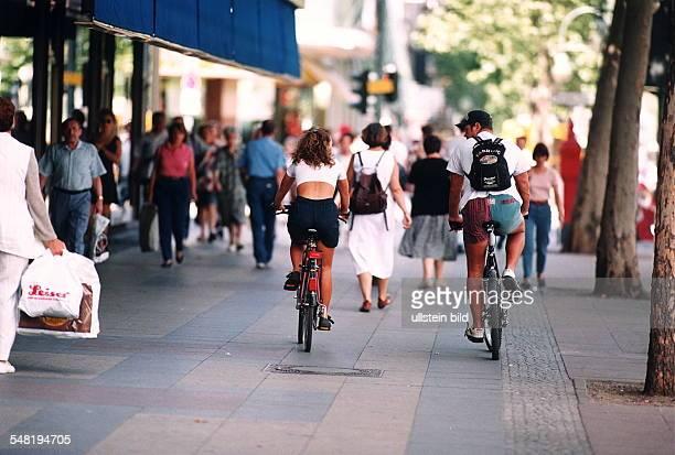 Fehlverhalten im Straßenverkehr: zwei Fahrradfahrer fahren nebeneinander auf dem Gehweg links der Straße - 1995