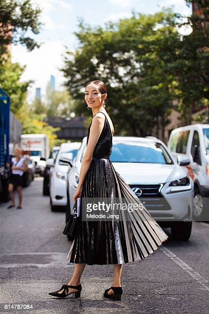 Fei Fei Sun attends the Proenza Schouler show by Lexus car in a Proenza Schouler black sleeveless dress with a black and white pleats and black shoes...