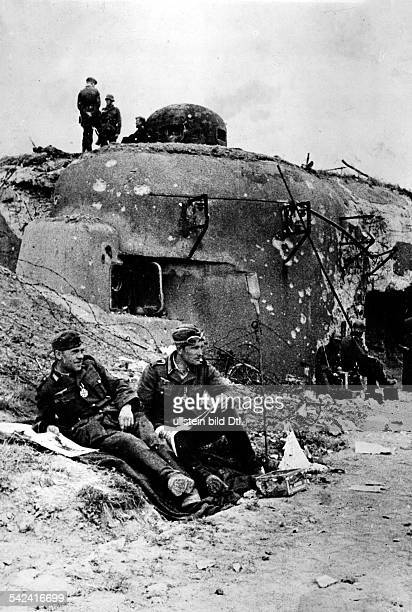 WK II Feldzug gegen Frankreich Zwei deutsche Soldaten sitzen vor einem eroberten Panzerwerk der MaginotLinie fuer die Eroberung wurden sie mit dem...
