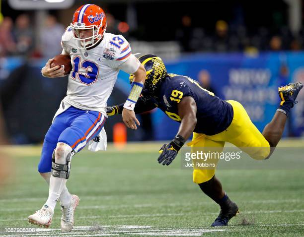 Feleipe Franks of the Florida Gators is pursued by Kwity Paye of the Michigan Wolverines in the second quarter during the ChickfilA Peach Bowl at...