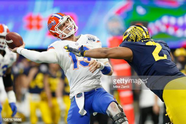 Feleipe Franks of the Florida Gators throws under pressure from Carlo Kemp of the Michigan Wolverines in the first quarter during the ChickfilA Peach...