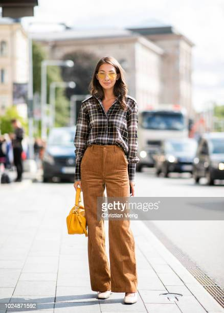 Felicia Akerstrom Ma wearing checked button shirt, corduroy pants is seen during Stockholm Runway SS19 on August 28, 2018 in Stockholm, Sweden.
